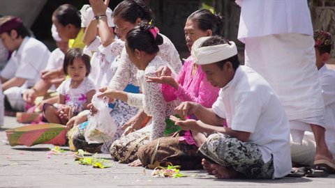 Indonesia. bali. March 7.2016. Balinese priest performing ritual, man and woman pray on ceremony and making offering