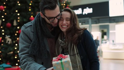 Close up young man hugging girlfriends and gives Christmas gift in the mall background Christmas tree couple shopping family woman love relationship romantic smiling celebrating slow motion