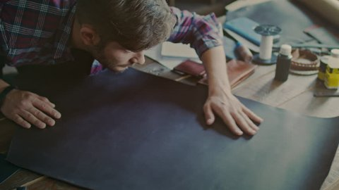 Leather worker looking at leather material on table. Top view of craftsman working with leather. High angle view of man touching piece of leather on table at workshop