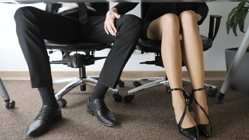 Office harassment. A beautiful girl young man in a suit is sexually harassing young man in the office. Touching the girl for the knee