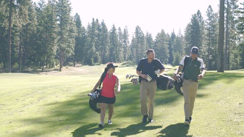 Three people walking on a golf course carrying golf bags