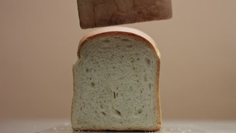 front view of brick of bread. Mans hand take off a front part of bread to show the inner part of bread. Bread texture