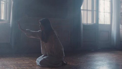 Young woman in long nighty sits on her knees in a dark room, she reaches out her hand and feels something in the air, scared she walks away. Paranormal activity, mystery