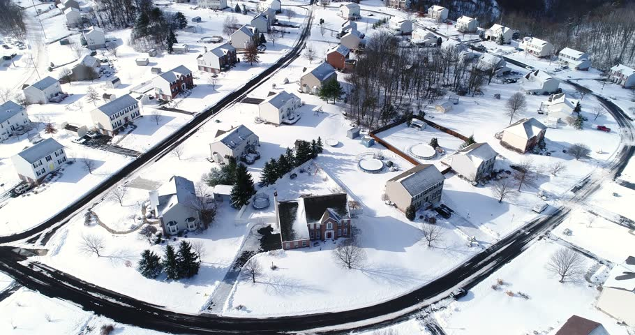A slow forward tilt-up winter aerial establishing shot of snow covered roads and homes in a rust belt upscale residential neighborhood. Factory smokestacks in the distance. Pittsburgh suburbs.