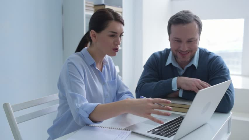 Two heads are better than one. Millennial colleagues sitting at a table and discussing their project while looking at a screen of a laptop and taking some noted. | Shutterstock HD Video #34864369