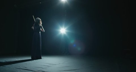 a talented girl violinist performs at her first solo concert, stage light, dark background