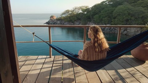 4k Adult woman sitting in hammock, relaxing on deck of exotic beach hut / bungalow at holiday resort.