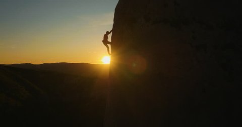 Aerial of a man silhouette climbing up the wall at amazing sunset.