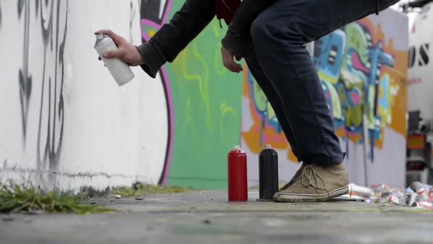 Juvenile delinquent, using spray paint to create graffiti on a concrete wall