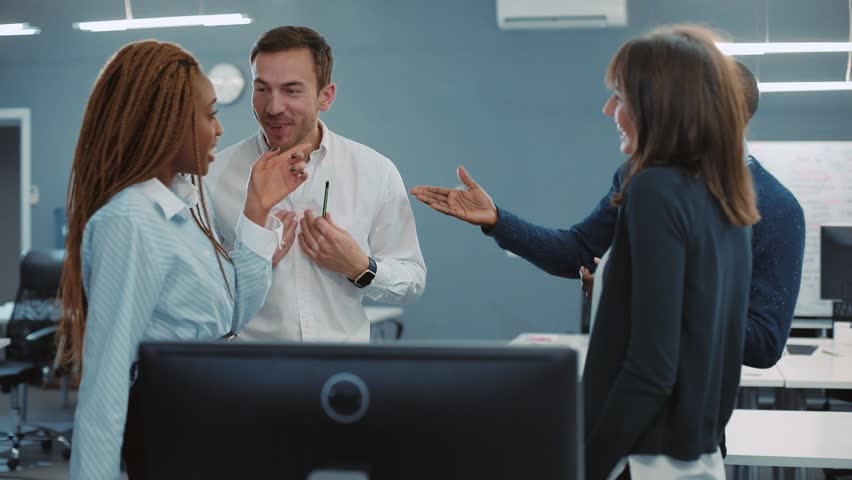Four friends discussing plans for Friday evening at firm's office. Young people talking, actively gesticulating. End of working week. Indoors. | Shutterstock HD Video #34937704
