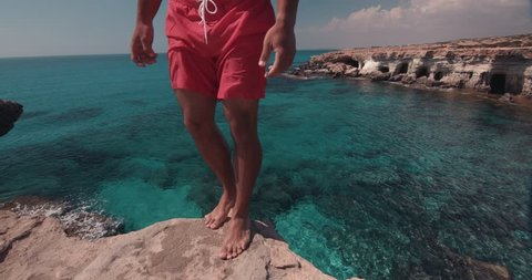 Sporty man jumping off cliff with somersault and diving into tropical island blue sea water