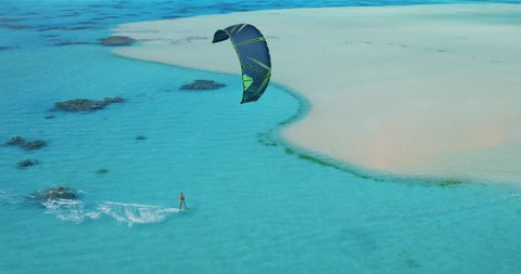 Cinematic aerial view of kiteboarder gliding across tropical ocean