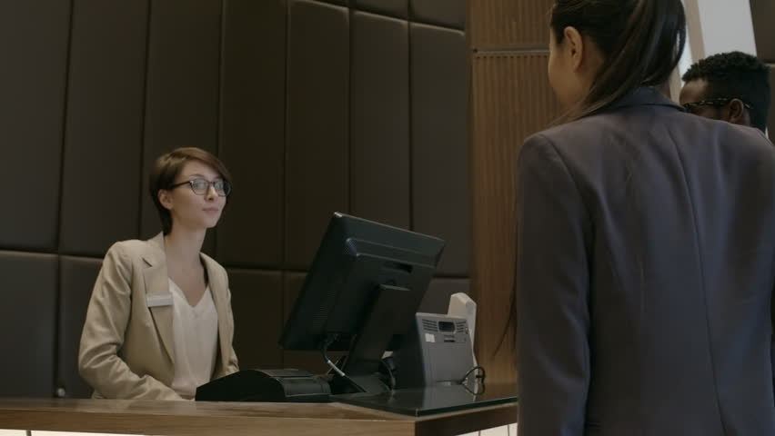 Rear view of businessman and businesswoman pulling suitcases and walking to check–in desk. Friendly female receptionist greeting guests and talking with them