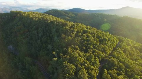 Forward flight over forested hills in Australian alps at sunset