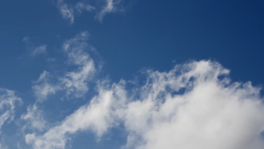 White fluffy clouds moving fast in the clear blue sky