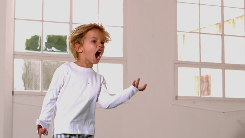 Boy in pajamas jumping and shouting in front of window in slow motion