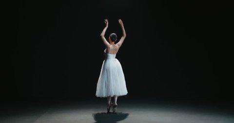 beautiful Asian girl ballet dancer dancing on black background slow motion
