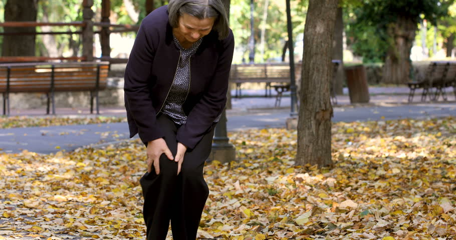 Senior woman walking in autumn park and having knee pain. Arthritis pain concept. The person comes in focus.