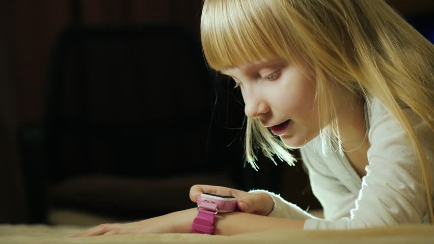 Blonde-haired girl 6 years old talking on mobile phone, using smart wrist watch | Shutterstock HD Video #35010469