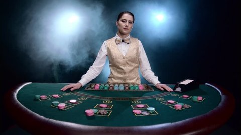 Croupier deals the cards from the card holder on black smoky background with spotlights. Slow motion