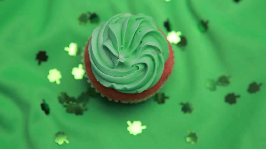 St patricks day cupcake revolving with shamrock confetti falling on green surface