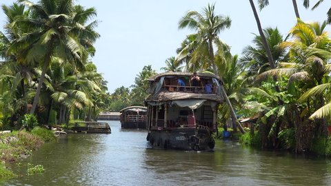 CIRCA 2010s - Houseboats travel on the backwaters of Kerala, India.