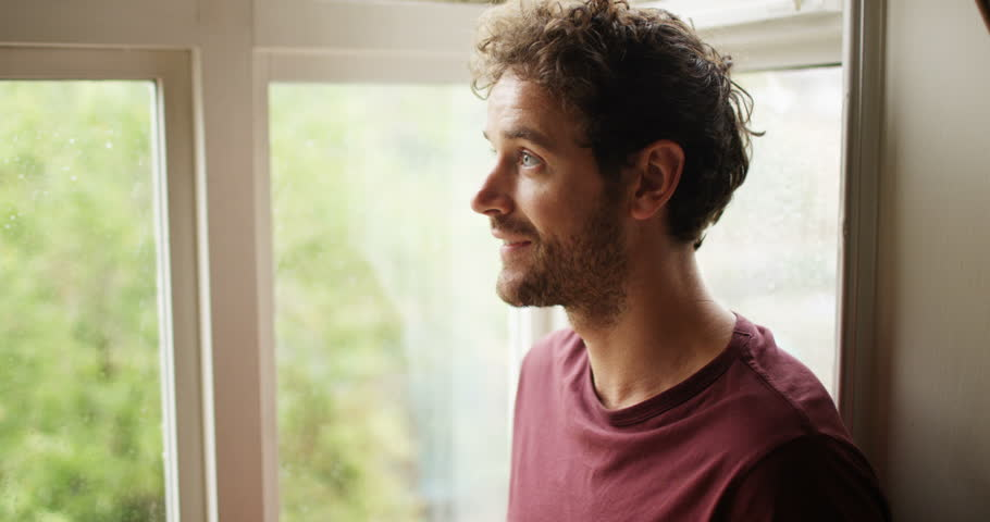4K Optimistic man looking out of window on a rainy day turns to smile at camera. Slow motion.