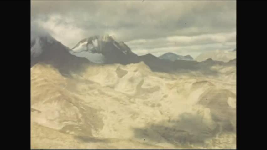 CIRCA - 1952 - Mountain ranges in Kodiak, Alaska are shot from a glider in daytime through sunset.