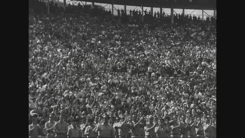 CIRCA - 1963 - JFK and Jackie Kennedy give speeches in a crowded stadium.