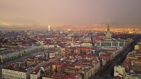 turin city aerial shot at sunrise flying towards mole antonelliana alps in the background