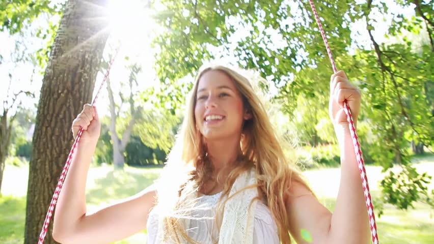 Young beautiful teenage woman is having fun on a swing. Slow Motion
