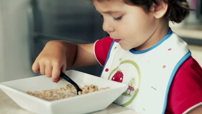 Little boy eating cornflakes with milk, slow motion shot at 120fps