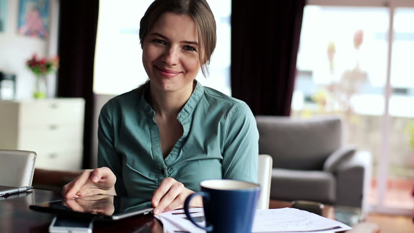 Happy businesswoman with tablet computer in home