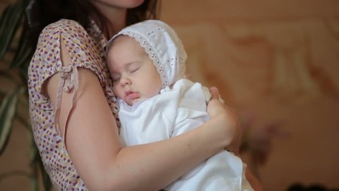 mother hugging baby at  ceremony of baptism
