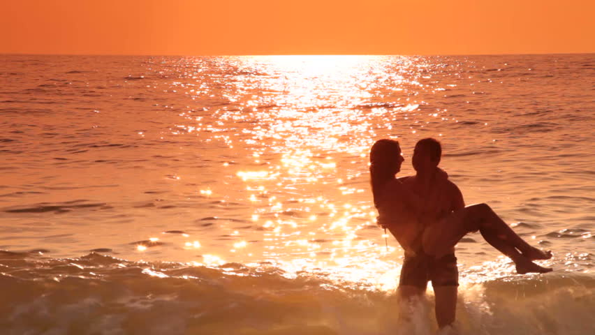 Romantic Teen Couple Kissing On The Beach At Sunset Stock