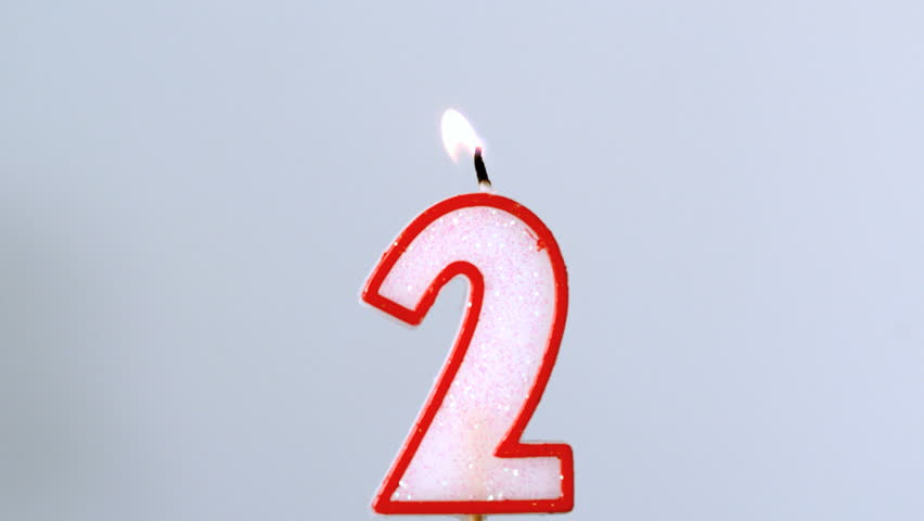 Two birthday candle flickering and extinguishing on blue background in slow motion