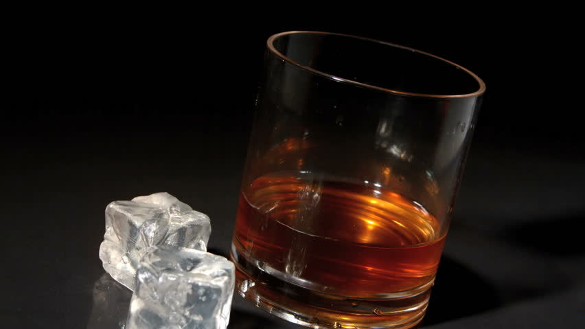 Ice cubes falling into tumbler of whiskey and ice in slow motion