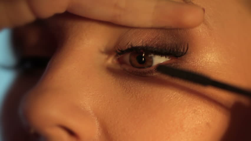 Make-up artist applying eyelash makeup to model's eye. Close up view.