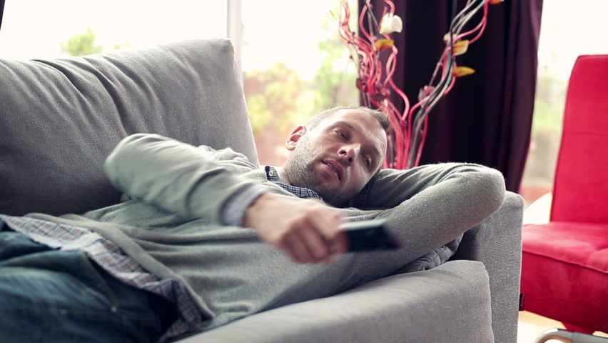 Stock Video Clip of Bored man on sofa watching tv at | Shutterstock