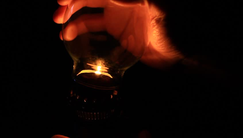 How to light an oil lamp. Light concept. Man preparing an old fashioned lantern in darkness.