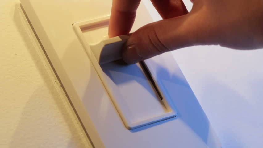 Close up of woman's hand comes into frame, turns on dimmer switch and adjusts to correct setting, shot in HD video