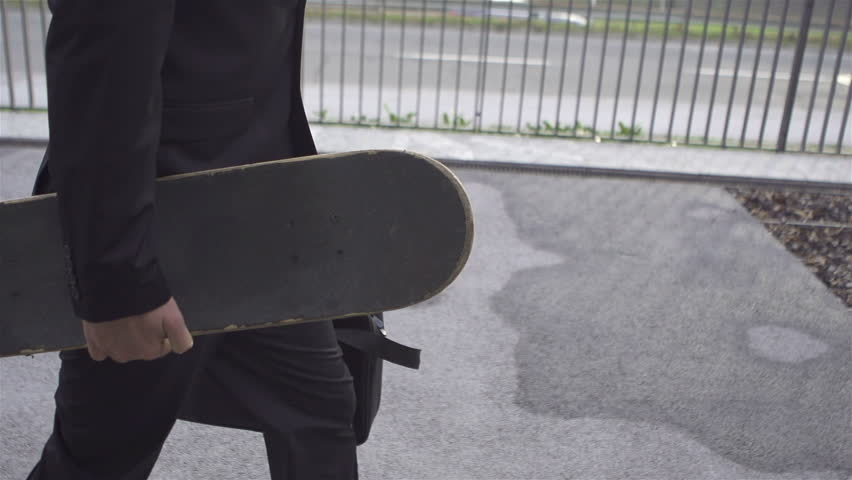 SLOW MOTION: Young businessman with skateboard