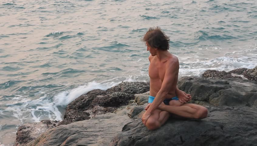 Young man doing yoga exercise in the lotus position on the deserted wild stone sea beach (HD) | Shutterstock HD Video #3581609