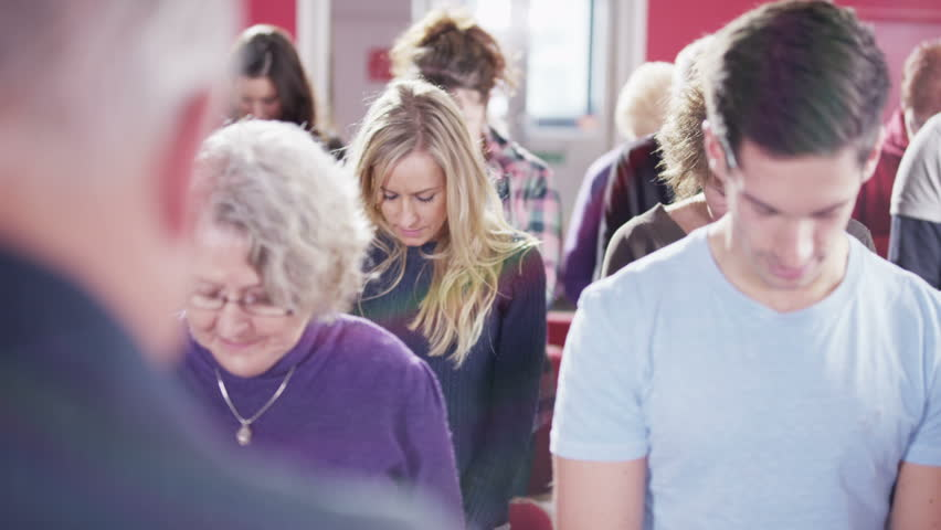 Informal contemporary church group of mixed age and race bow their heads  and begin to pray