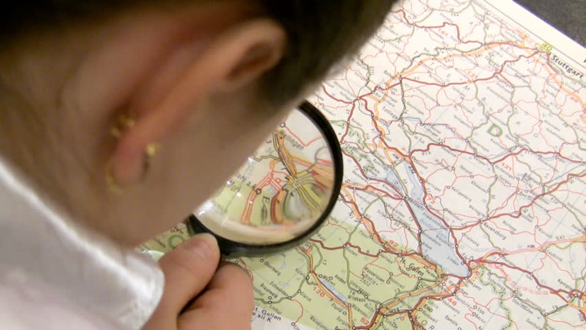 girl with a magnifier studies a map of Europe.