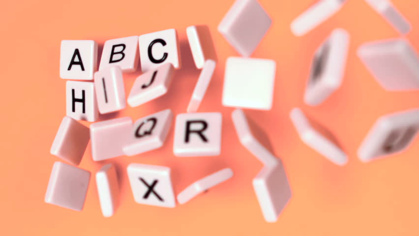 Plastic letters bouncing and showing alphabet on orange surface in slow motion