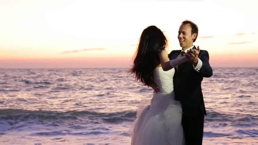 Newlyweds are dancing on the seashore.