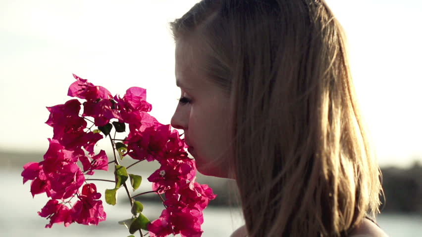 Young woman standing on seashore and smelling flower, slow motion shot at 240fps