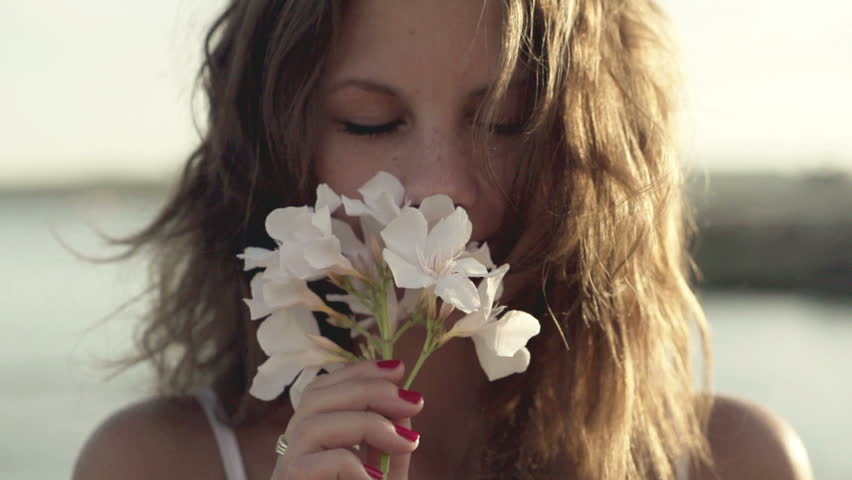 Young woman standing on seashore and smelling flower, slow motion shot at 120fps
