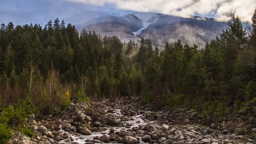 Misty Clouds on a Snowy Mountain Top and River Running. Shot in BC, Canada. Photo Sequence shot in RAW and Post-Production in After Effects.